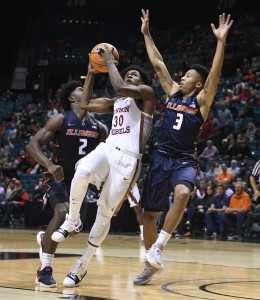 UNLV Rebels guard Jovan Mooring (30) drives between Illinois Fighting Illini forward Kipper Nichols (2) and Illinois Fighting Illini guard Te'Jon Lucas (3) during their NCAA basketball game Saturday, December 9, 2017, at the MGM Grand Garden Arena. UNLV won the game 89-82.  CREDIT: Sam Morris/Las Vegas News Bureau